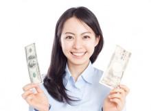 円とドルの紙幣を持った女性